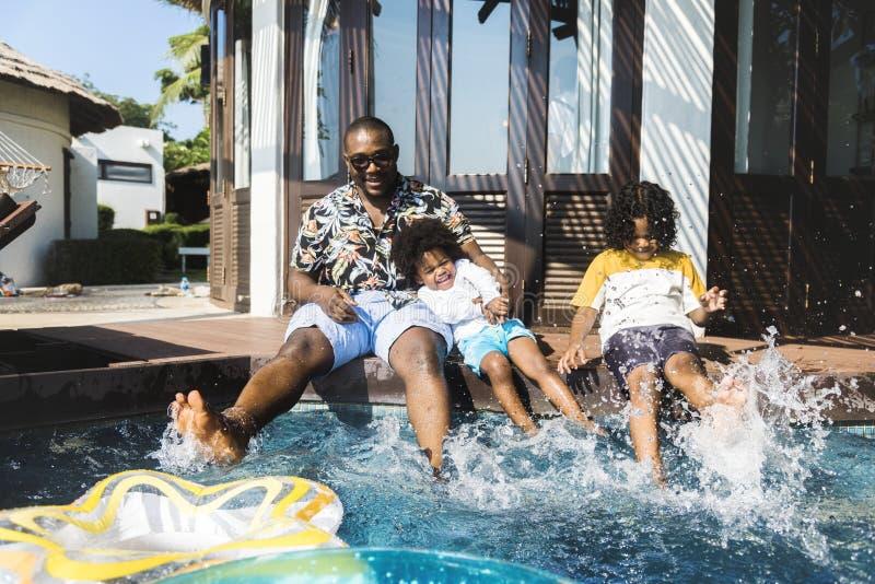 Famille jouant par une piscine image stock