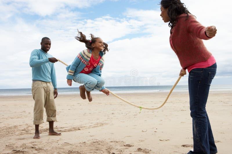Famille jouant sur la plage image stock