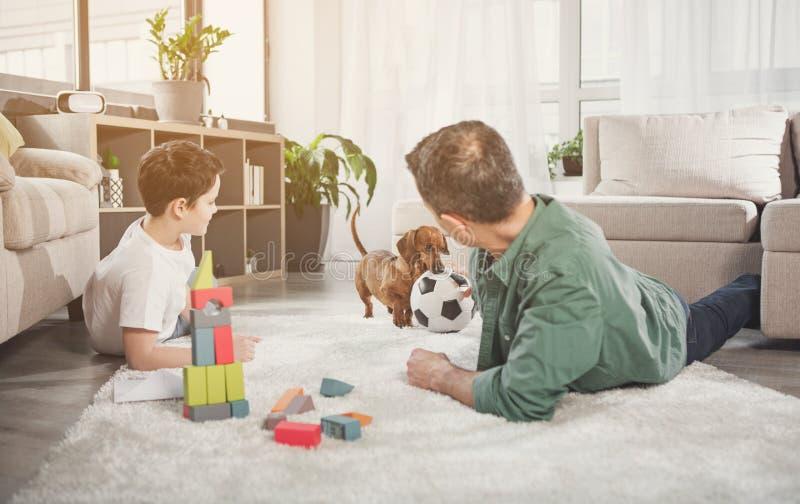 Famille joyeuse ayant l'amusement avec l'animal familier dans la maison photo libre de droits