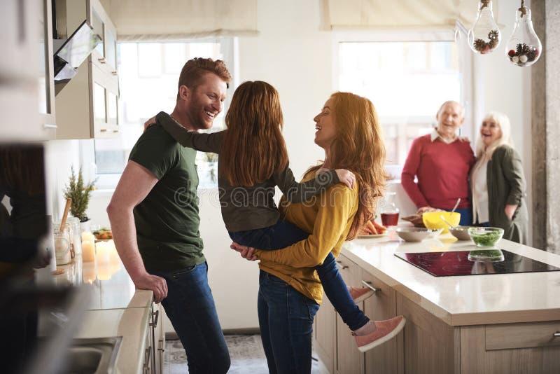 Famille joyeuse ayant l'amusement avec l'enfant dans la cuisine images libres de droits