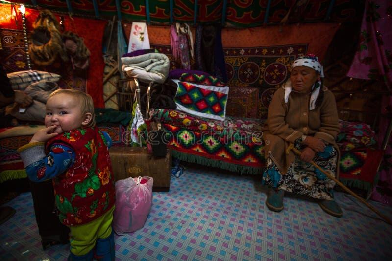 Famille kazakh des chasseurs avec les aigles d'or d'oiseaux de chasse à l'intérieur du Yurt mongol images libres de droits