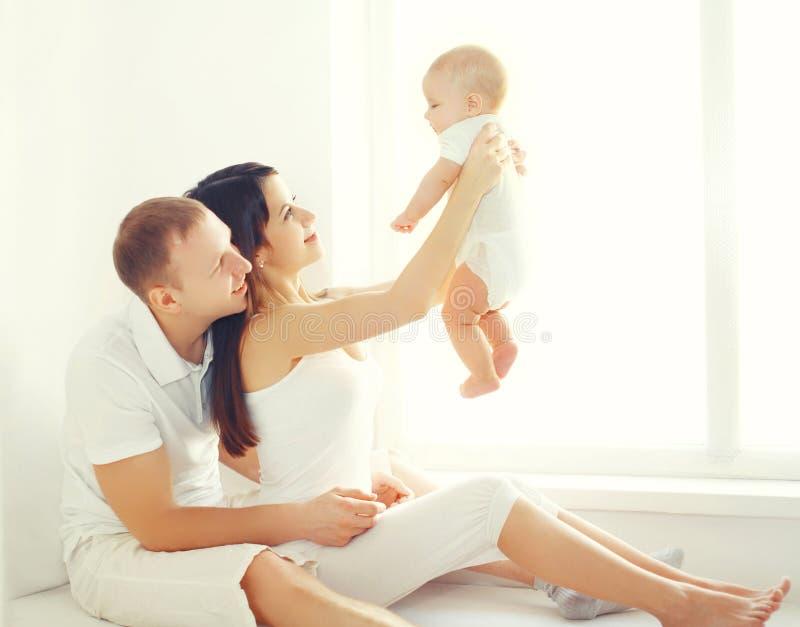 Famille, mère heureuse et père jouant avec la maison de bébé dans la chambre blanche photo stock