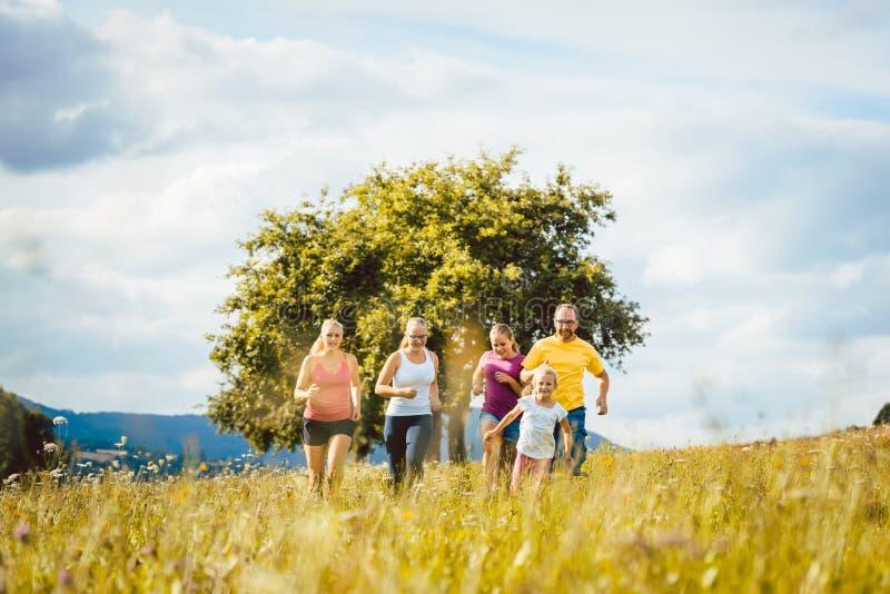 Famille, mère, père et enfants courant pour le sport photo libre de droits