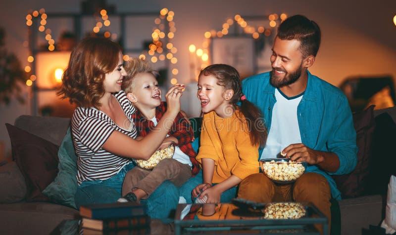 Famille mère père et enfants regardant projecteur, télévision, films avec pop-corn le soir à la maison photo stock