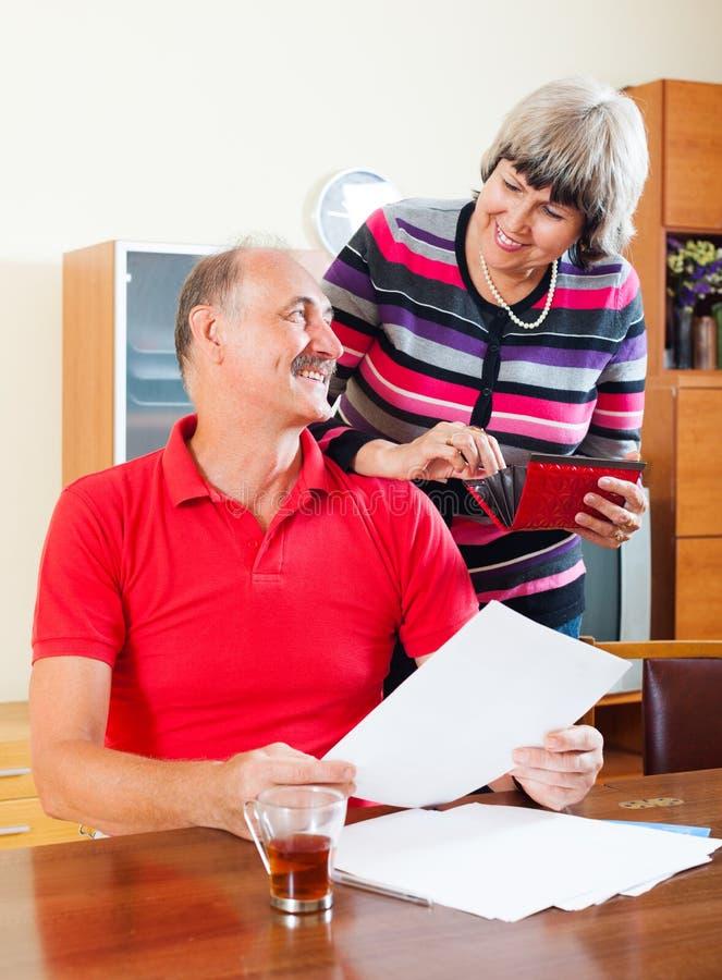 Famille mûre heureuse avec les documents financiers photographie stock libre de droits
