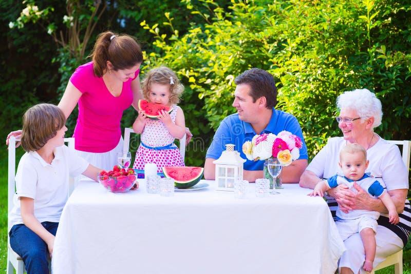 Famille mangeant du fruit dans le jardin image libre de droits