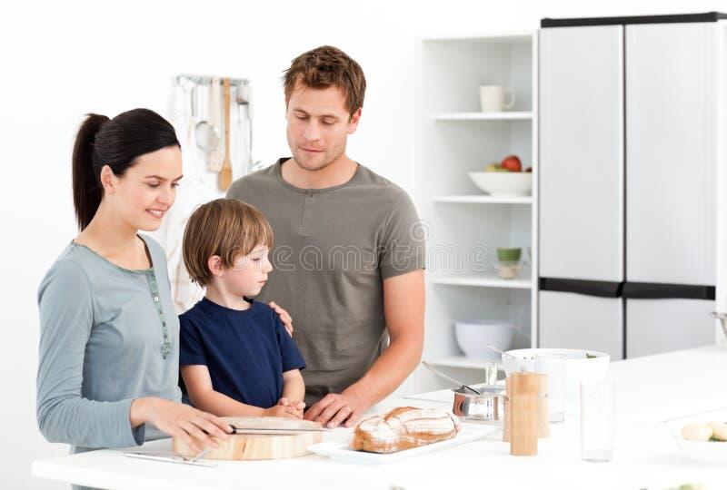 Famille mangeant du pain dans la cuisine photos libres de droits