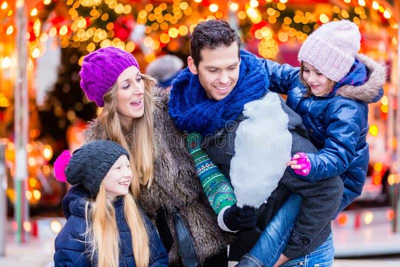 Famille mangeant la sucrerie de coton sur le marché de Noël images libres de droits