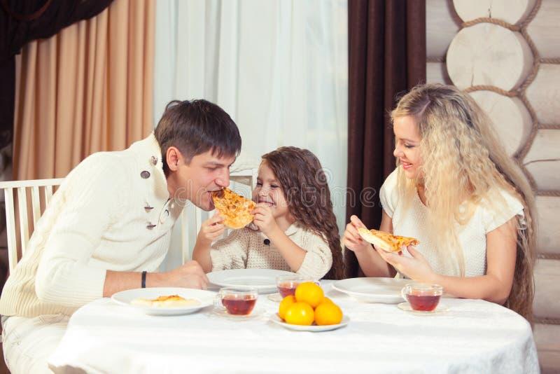 Famille mangeant le dîner à une table de salle à manger, table ronde, pizza, orange, maison faite de bois photos stock