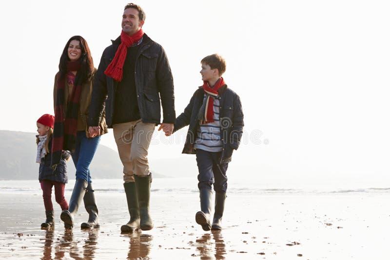 Famille marchant le long de la plage de l'hiver image stock