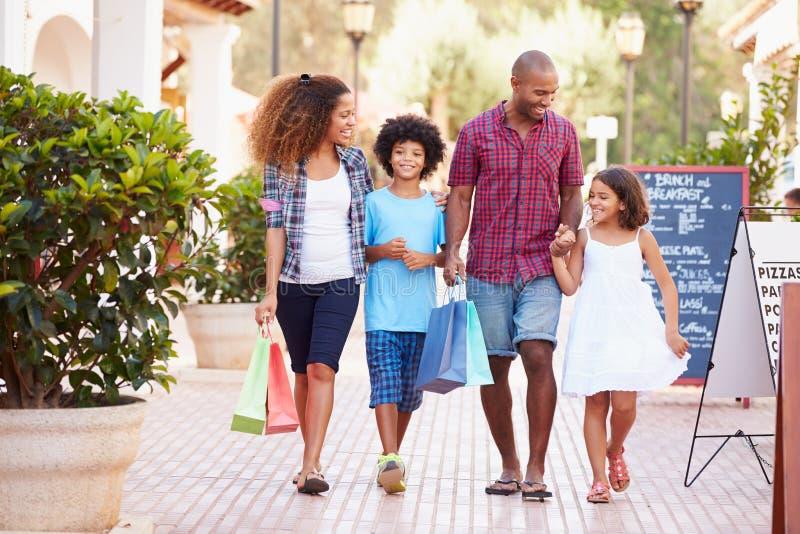 Famille marchant le long de la rue avec des paniers photos stock