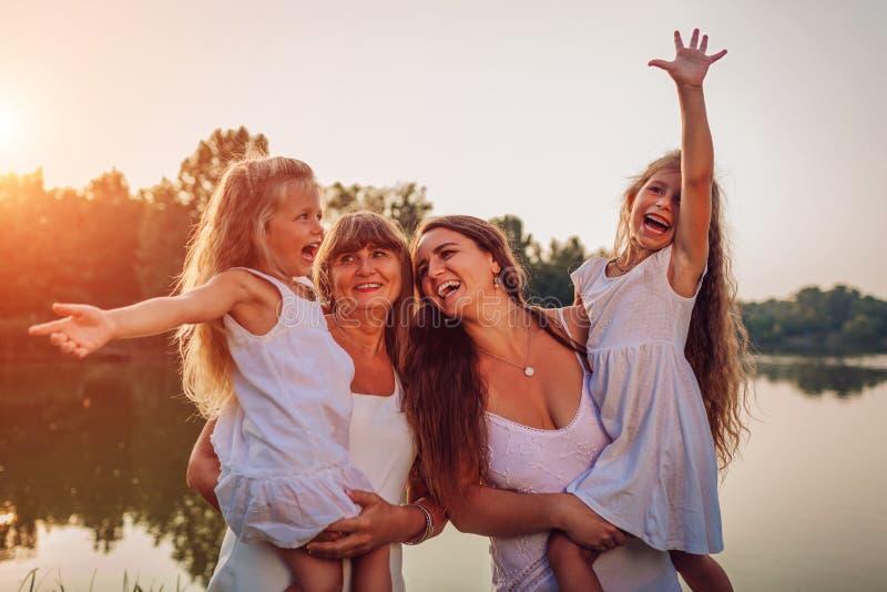 Famille marchant par la rivière d'été au coucher du soleil Mère et grand-mère tenant des enfants et rire Trois denerations image libre de droits