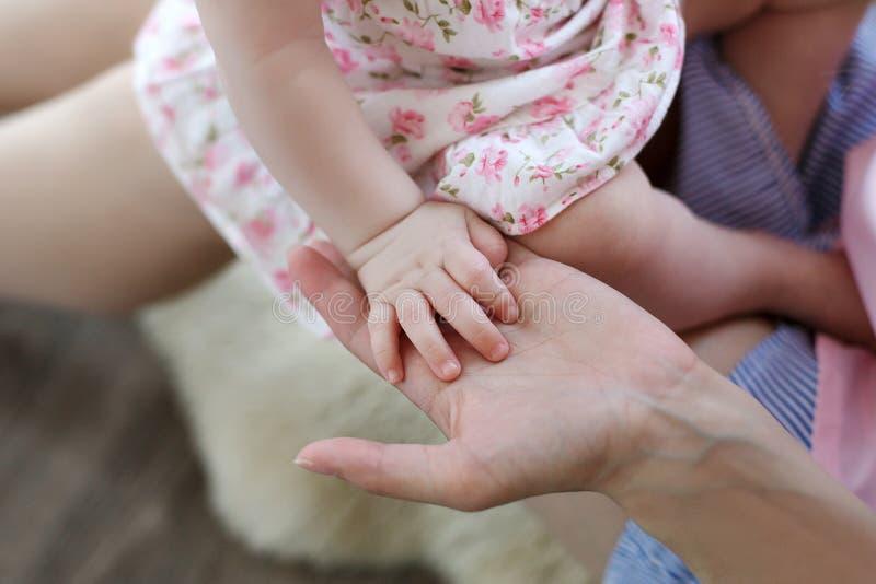Famille, maternit?, parenting, les gens et concept de garde d'enfants - fermez-vous de la m?re et des mains nouveau-n?es de b?b? image stock