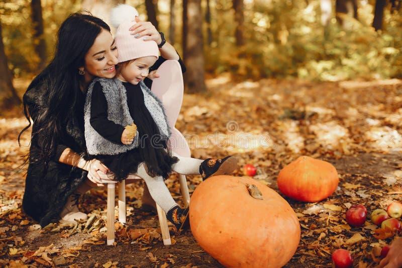 Famille mignonne et élégante en parc d'automne photographie stock libre de droits
