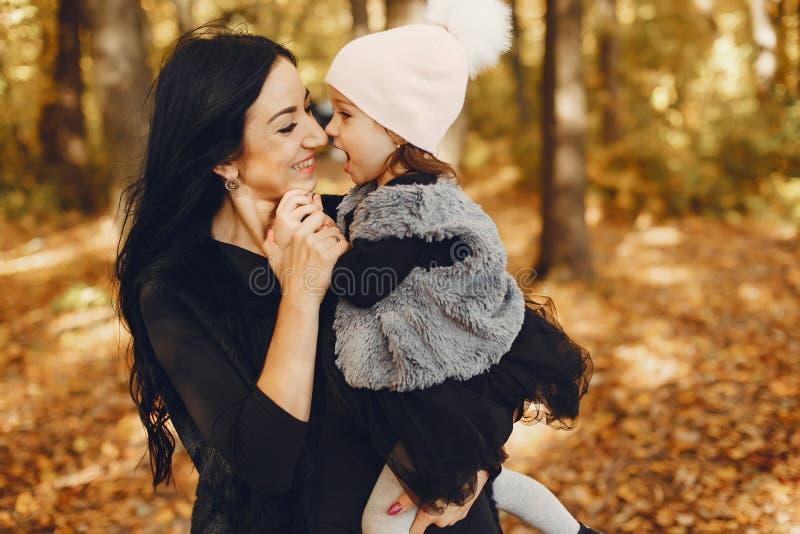 Famille mignonne et élégante en parc d'automne photo stock