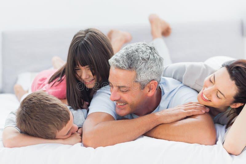 Famille mignonne se trouvant sur le lit et parlant ensemble images libres de droits