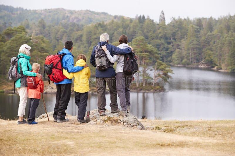 Famille multi de génération embrassant et admirant la vue de bord de lac, vue arrière, secteur de lac, R-U photos stock