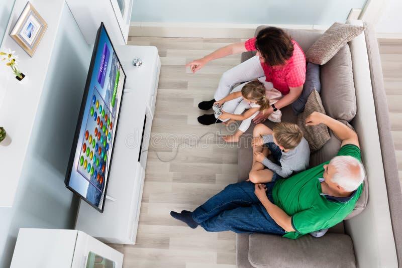 Famille multi de génération jouant le jeu vidéo à la maison photo stock