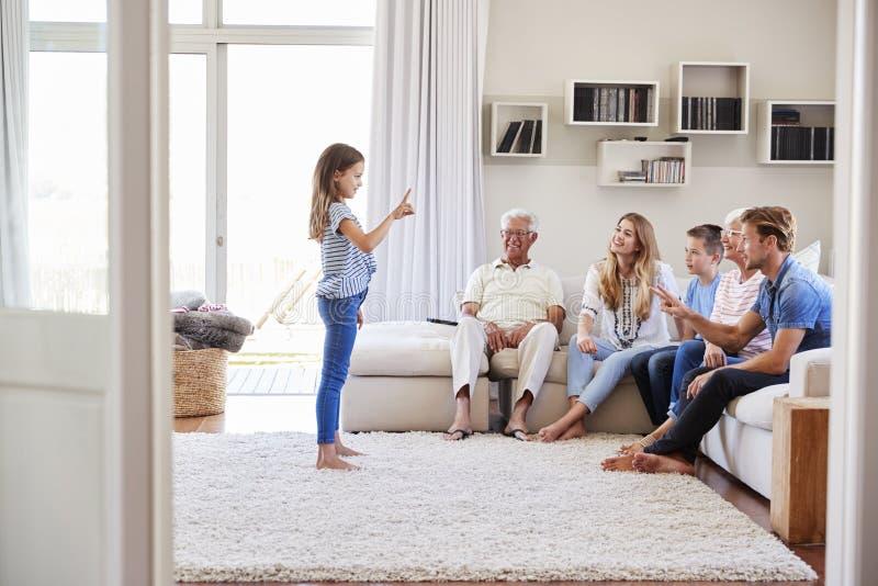 Famille multi de génération se reposant sur Sofa At Home Playing Charades image stock