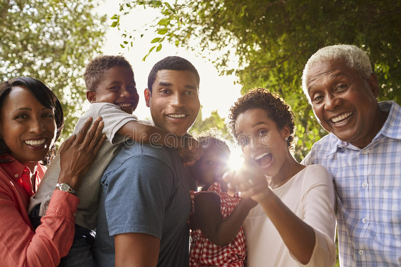 Famille multi de noir de génération dans le regard de jardin à l'appareil-photo photos libres de droits