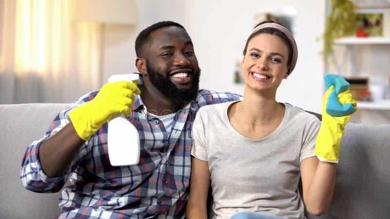 Famille multi-ethnique heureuse dans les gants avec le jet et l'éponge de détergent, householding photo libre de droits