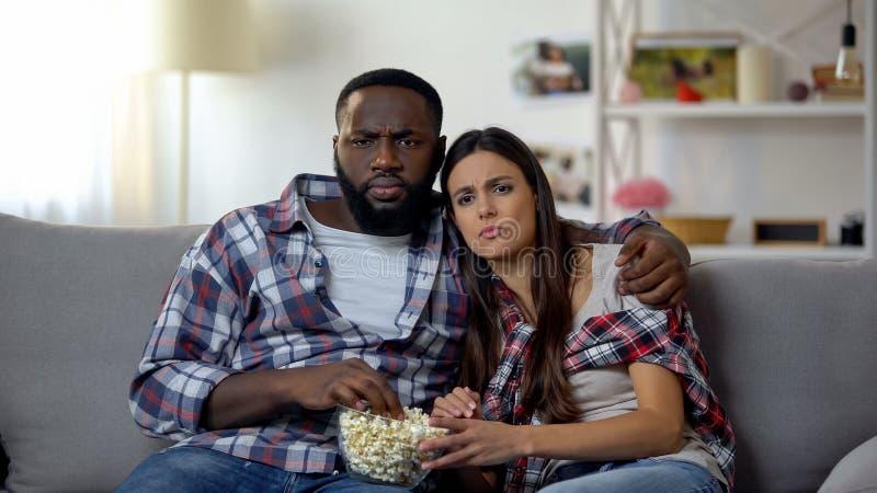 Famille multi-ethnique mangeant du maïs de bruit et observant le feuilleton à la maison, relaxation images libres de droits