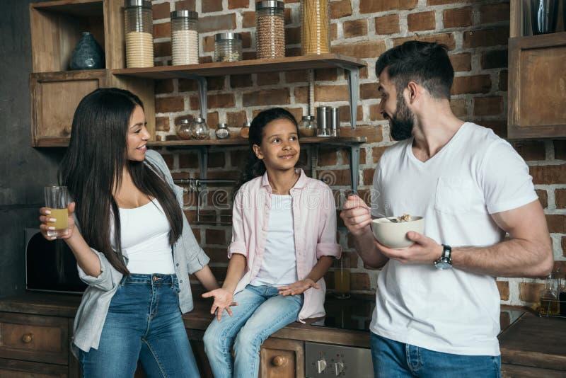 Famille multi-ethnique parlant tout en prenant le petit déjeuner à la cuisine photo stock