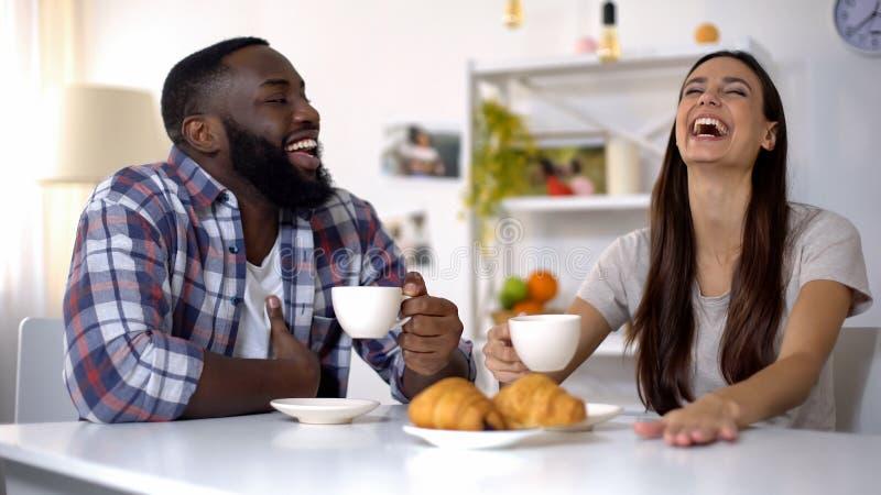 Famille multi-ethnique plaisantant et riant pendant le petit déjeuner à la maison, café de matin photo stock