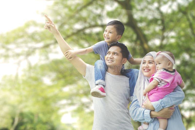 Famille musulmane regardant quelque chose en parc photographie stock libre de droits