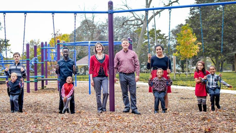 Famille nombreuse au parc sur Swingset photo libre de droits