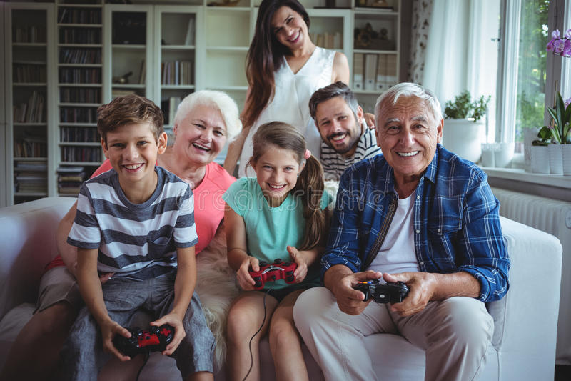 Famille observant les enfants jouer le jeu vidéo image libre de droits