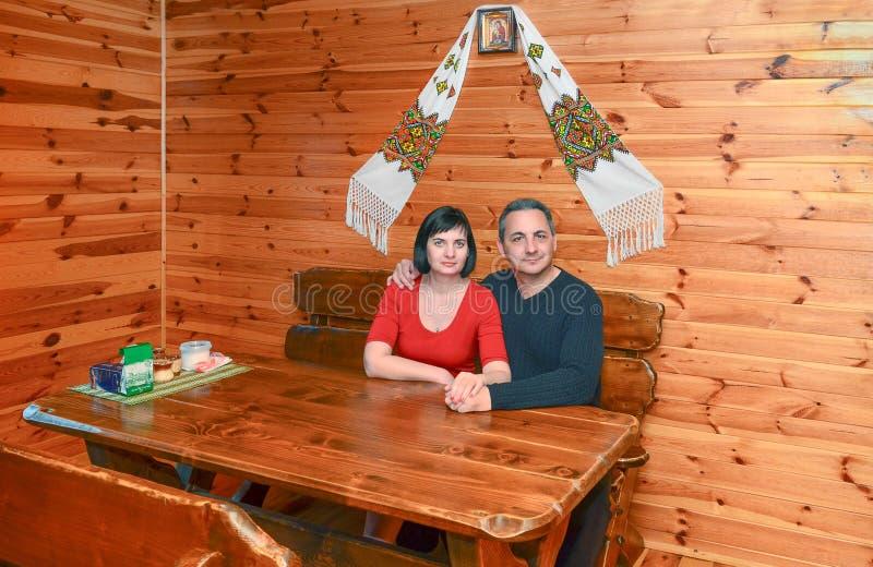 Famille orthodoxe, le couple se reposant à la table en bois sous l'icône photos stock