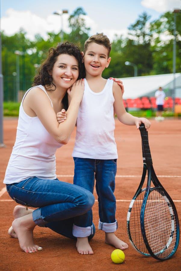 Famille ou mère mignonne et fils jouant le tennis et posant devant le tribunal extérieur photos libres de droits
