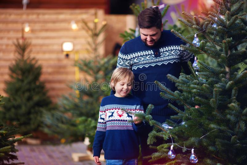 Famille, père heureux et fils achetant un arbre de Noël pendant des vacances d'hiver au marché saisonnier photographie stock