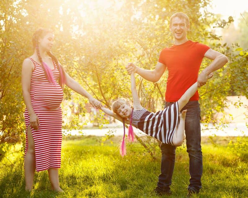 famille Père, mère enceinte et fille dehors image stock