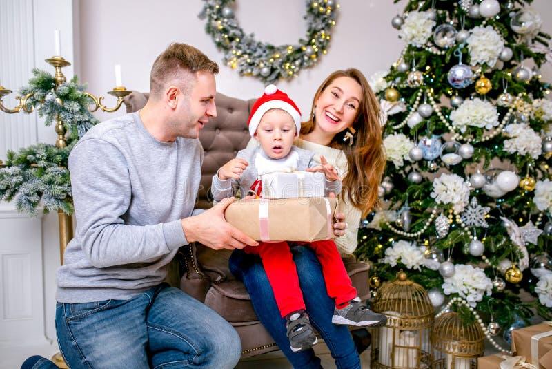 Famille, père, mère et fils heureux, pendant le matin dans le salon décoré pour Noël Ils ouvrent des présents et ont l'amusement  photographie stock