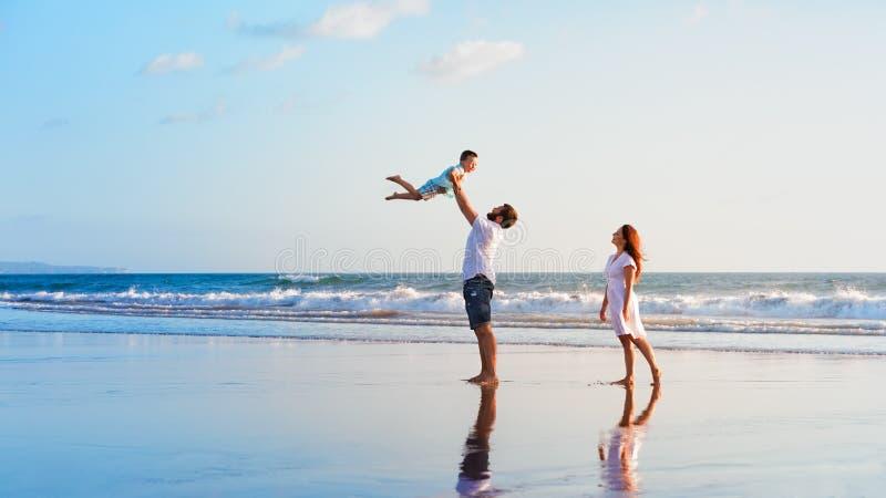 Famille - père, mère, promenade de bébé sur la plage de coucher du soleil photographie stock libre de droits
