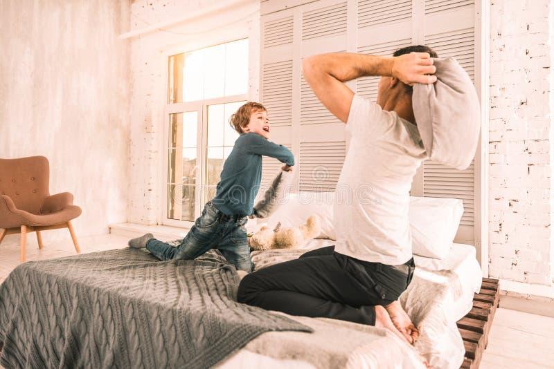 Famille parfaite aimante ayant l'amusement avec les oreillers photographie stock libre de droits