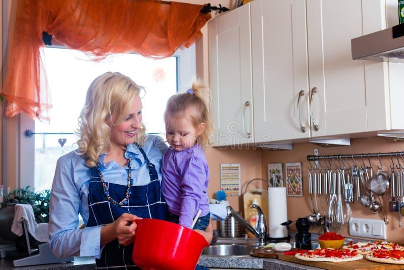 Famille - pizza de traitement au four de mère et d'enfant photos stock