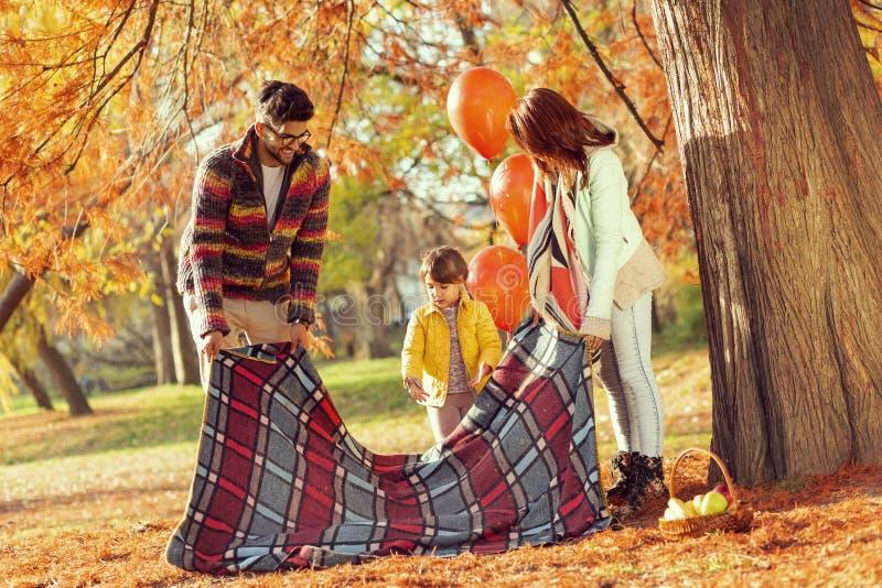 Famille plaçant une couverture de pique-nique image libre de droits