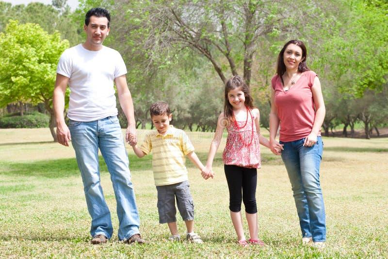 Famille posant à l'appareil-photo en stationnement photo stock