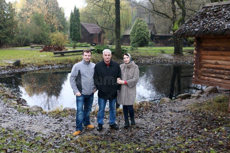 Famille posant sur le fond de l'étang photographie stock libre de droits
