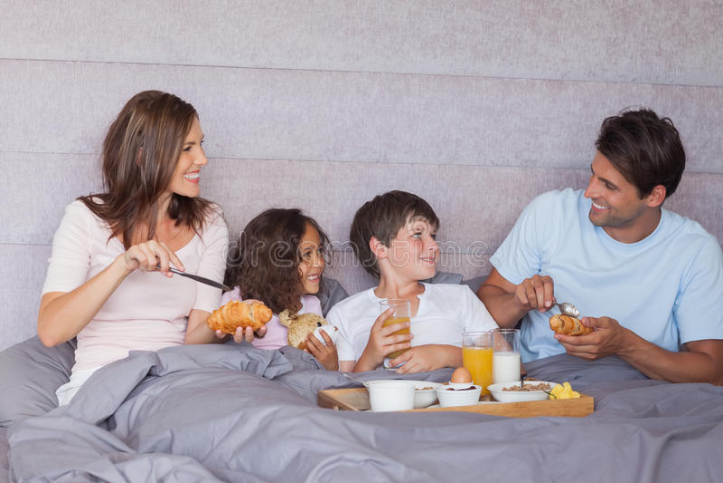 Famille prenant le petit déjeuner dans le lit images stock