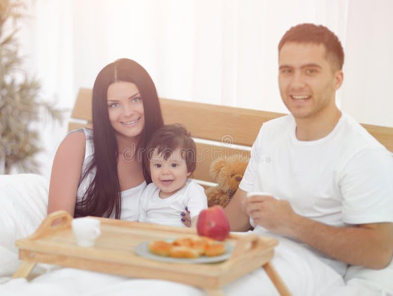 Famille prenant le petit déjeuner dans le lit à la maison image libre de droits