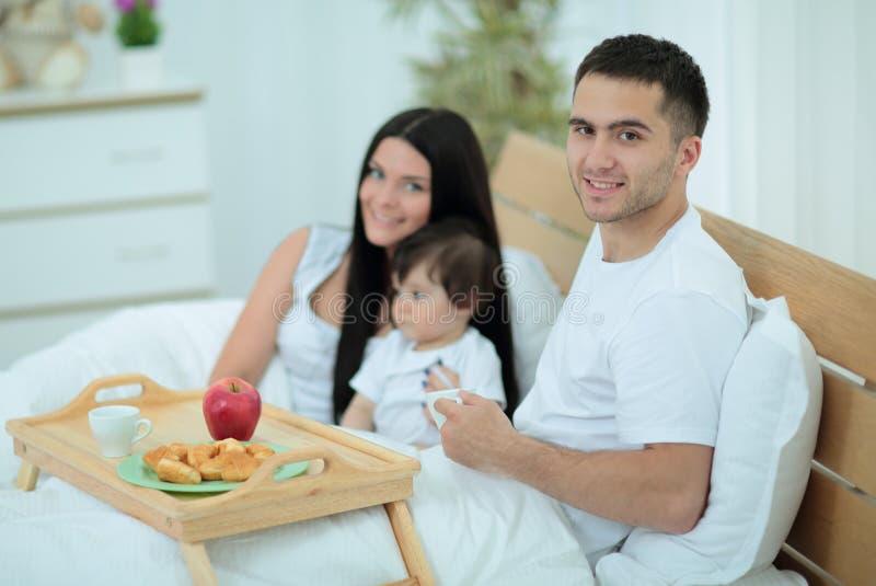 Famille prenant le petit déjeuner dans le lit à la maison photo libre de droits