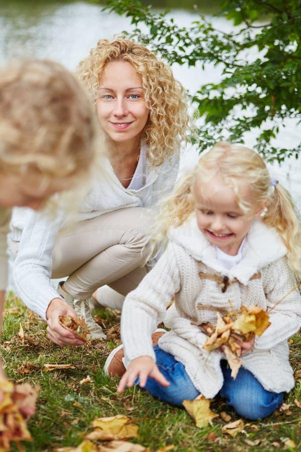 Famille rassemblant des feuilles en nature photo libre de droits