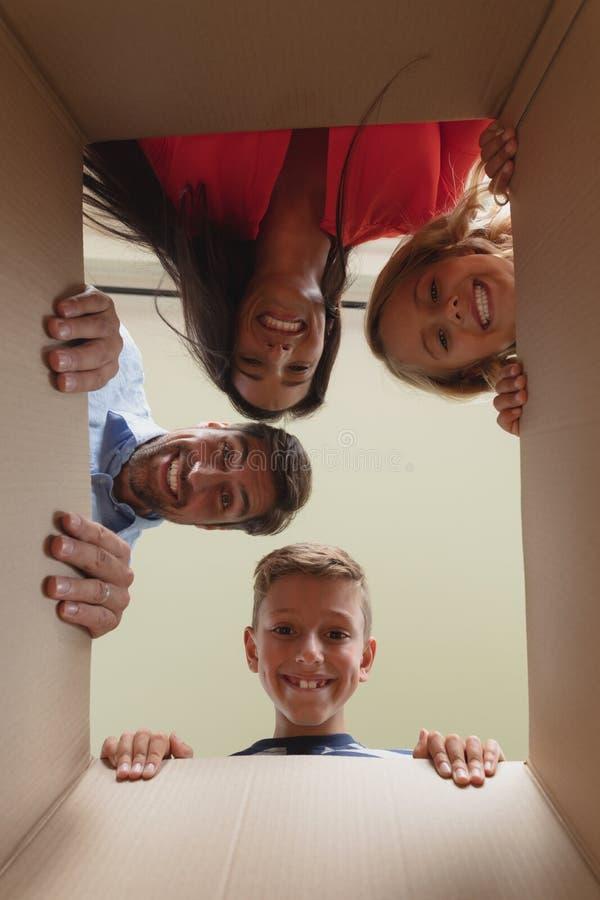 Famille regardant dans la boîte en carton à la maison photographie stock libre de droits
