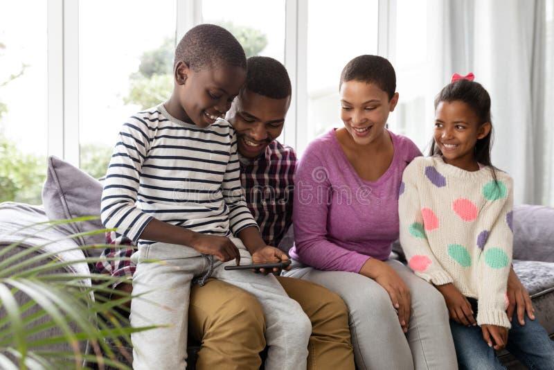 Famille regardant des photos au téléphone portable dans le salon photos libres de droits