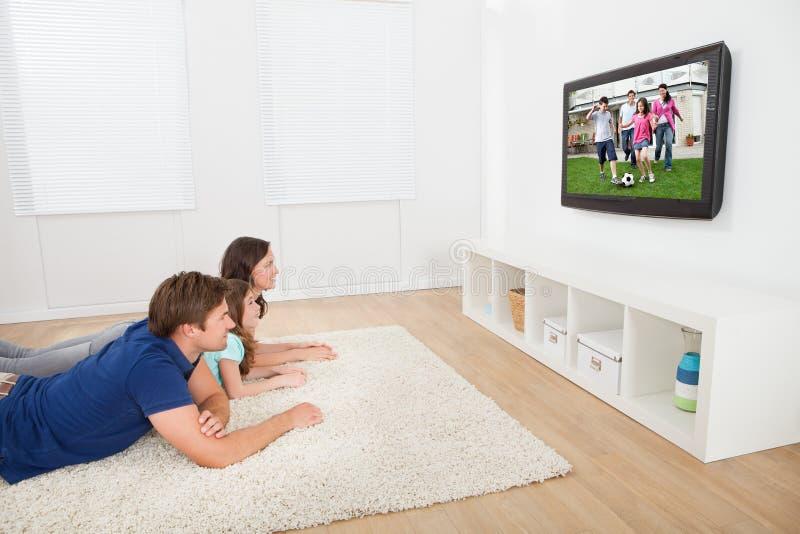 Famille regardant la TV à la maison image libre de droits