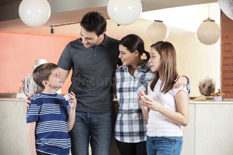 Famille regardant le garçon tenant la crème glacée au salon photos libres de droits